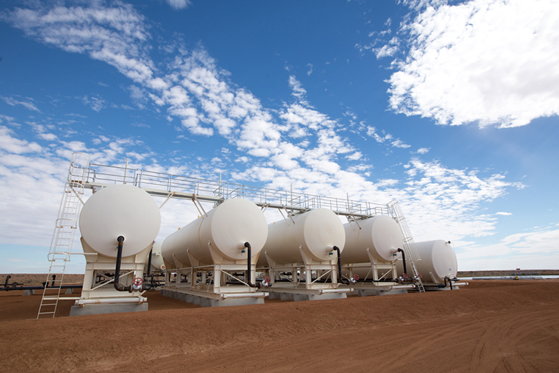Five white gas storage cylinders siting on the red earth of the Cooper Basin