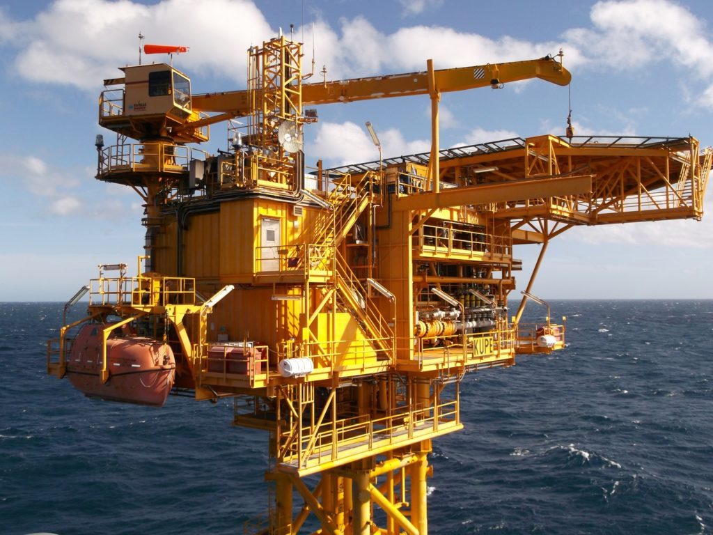 Bright yellow Kupe offshore platform with ocean and sky in background